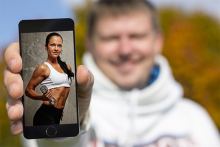 guy holding phone with video of fitness workout